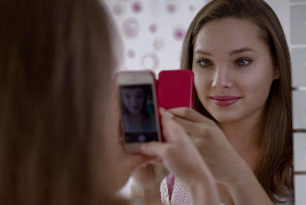 Beautiful teenager girl taking selfie in bathroom  with smartphone