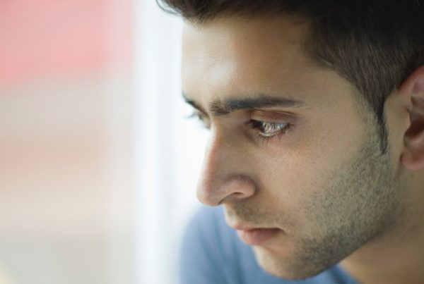 Indoor day time image in natural light of a serene Indian young man looking at view through glass window with blank expression. He is wearing blue t-shirt. One person, head and shoulders, horizontal composition with selective focus and copy space.