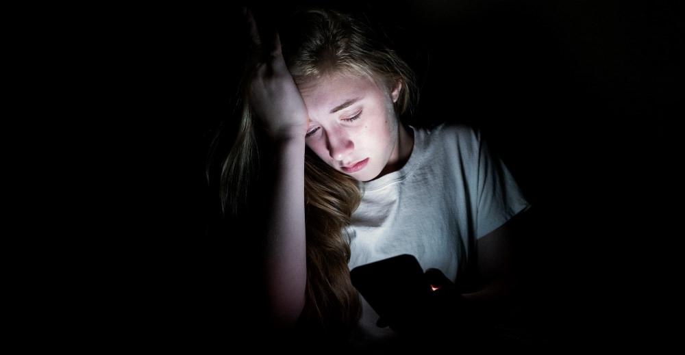child-self-generated-explicit-content-girl-sad-dark-phone